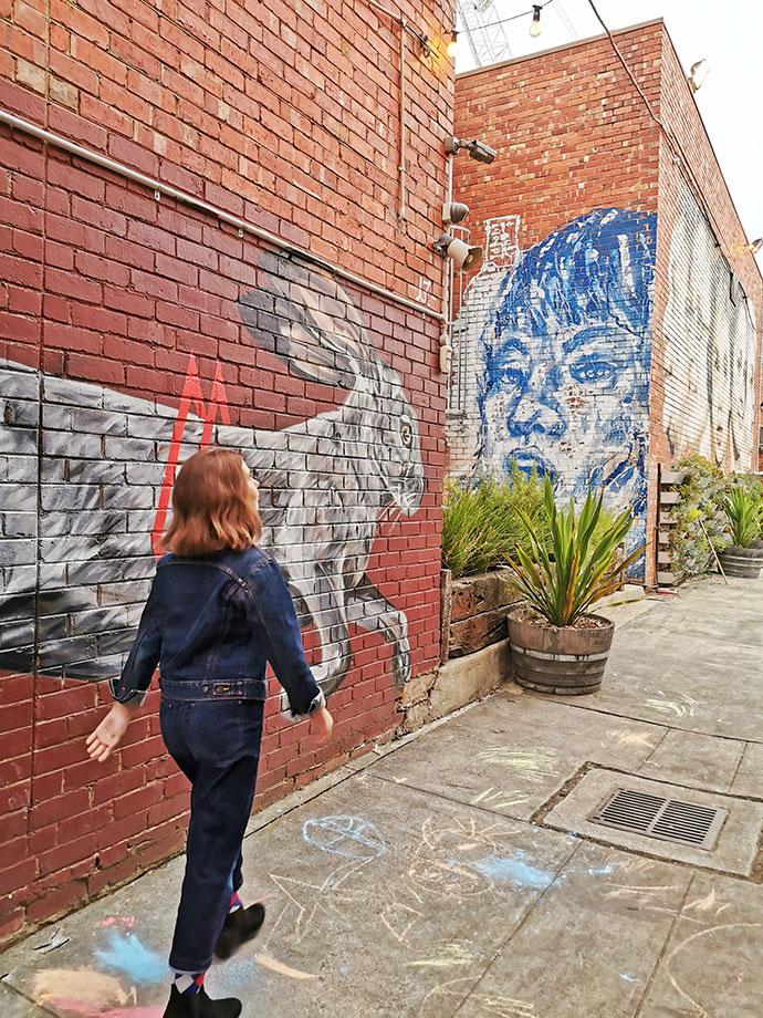 The backyard Ringwood, girl walking in alley with street art on walls