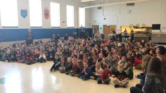 Belle Elementary School students sitting on the floor of the cafeteria
