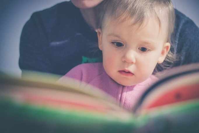 Toddler reading from a book