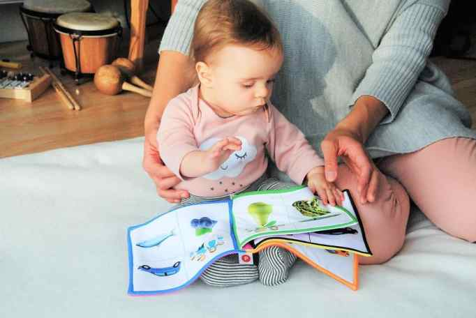 Child reading from book with illustrations