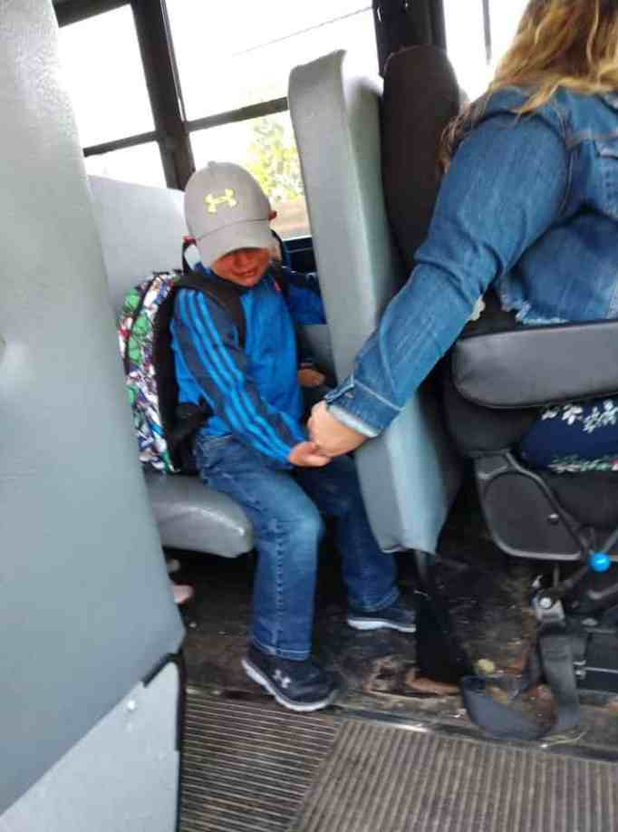 school bus driver holds boy's hand during 1st day of school jitters