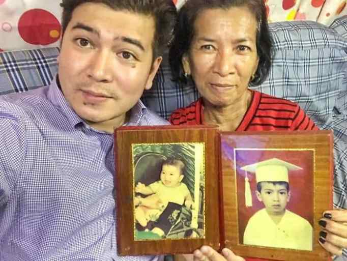 Jayvee together with his adoptive mother holding photos.