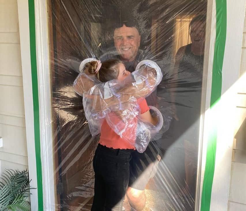 Grandpa hugging her grandkid through a plastic curtain.