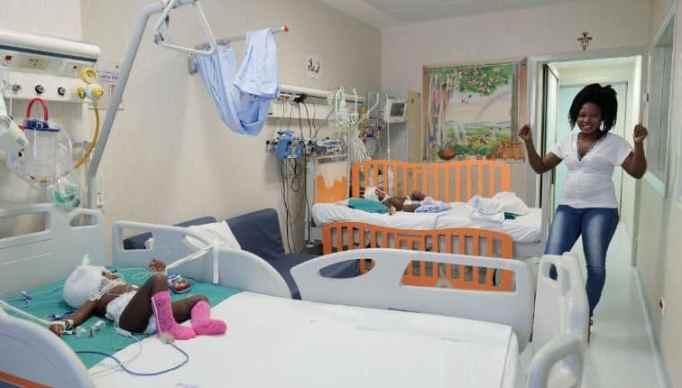 A joyful mom at a pediatric hospital looking at her babies.