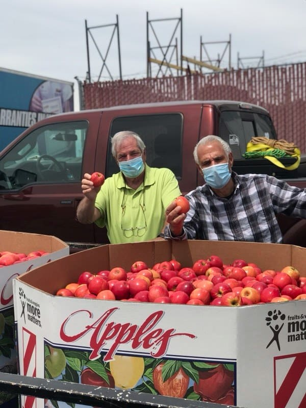 Two elderly men behind a container full of apples
