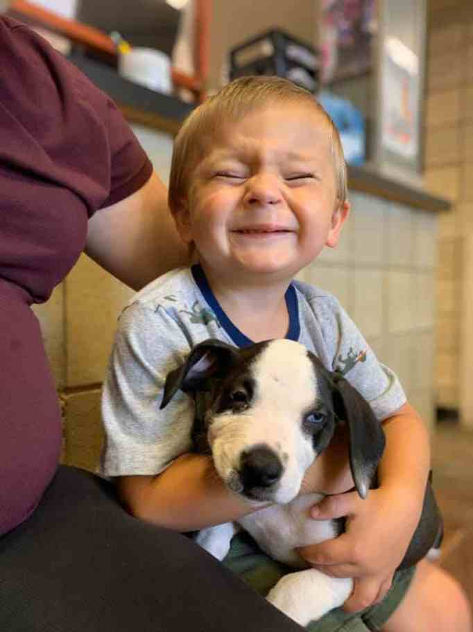 Bentley Boyers smiling while holding Lacey the puppy
