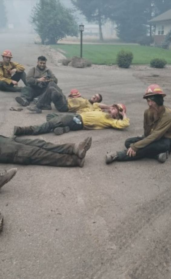 Oregon firefighters lying down on an ash-filled street