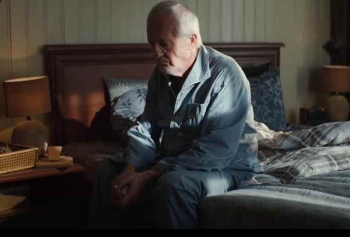 Sad grandpa sitting by the bed side all by himself.