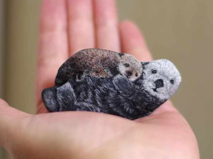 An image of an otter mother and offspring painted on a stone by Akie Nakata