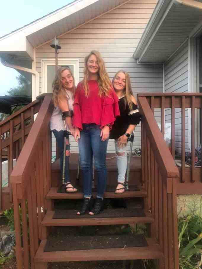 The Garrison triplets at home standing on their backyard porch.