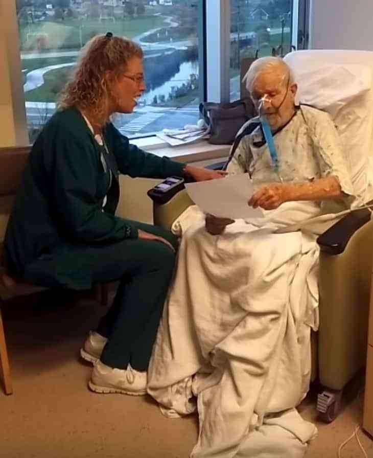 A nurse singing to her elderly patient in hospice care