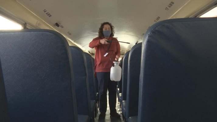 School principal Janet Throgmorton sanitizing a school bus