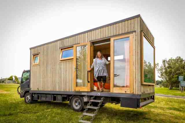 A woman standing in her off-grid tiny house truck