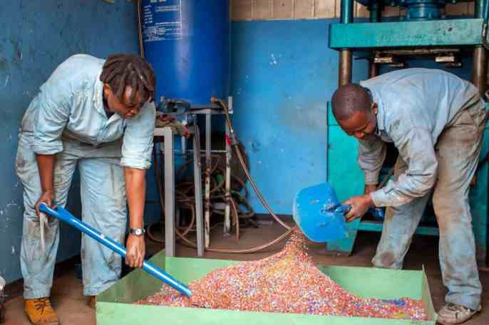 Nzambi Matee, a materials engineer and a man shoveling shredded plastic