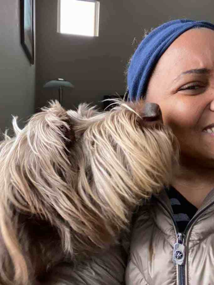 A dog licking a woman's face