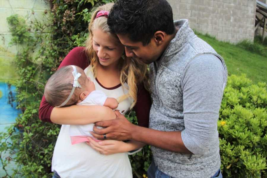 Addisyn with husband holding a baby in her arm