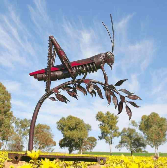 A gravity-defying metal sculpture of a grasshopper, crafted by Jordan Sprigg