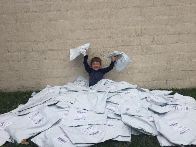 Ryan, packaging up shirt orders on his Ryan's Recycling Company.