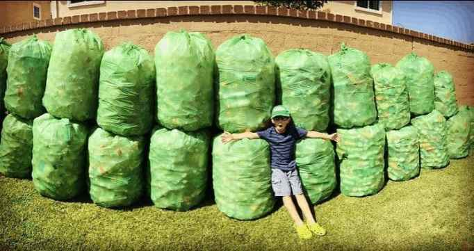 Ryan, the inspiring kid behind Ryan's Recycling Company poses for a picture with his packed recyclables.