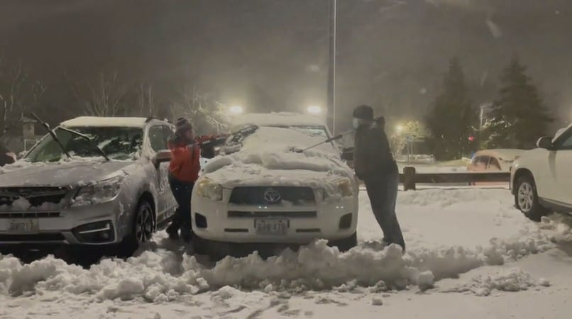 Two people cleaning snow off a car