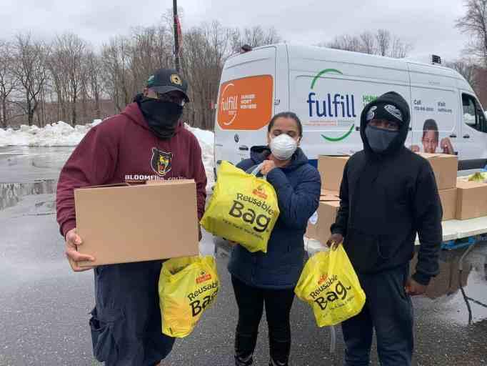 Volunteers carrying reusable bags full of supplies