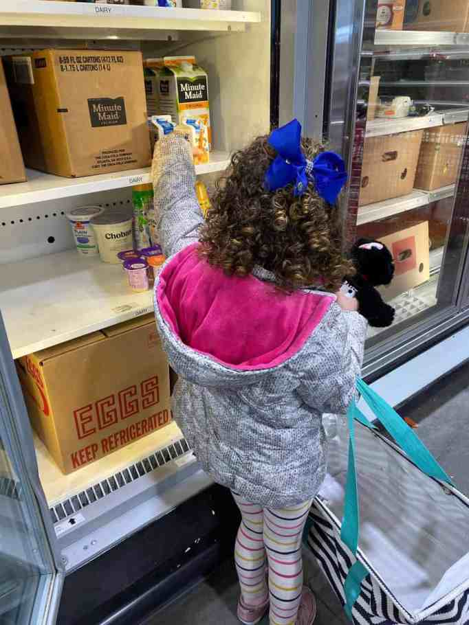 A little girl carrying a bag grabs food from Fulfill's food bank