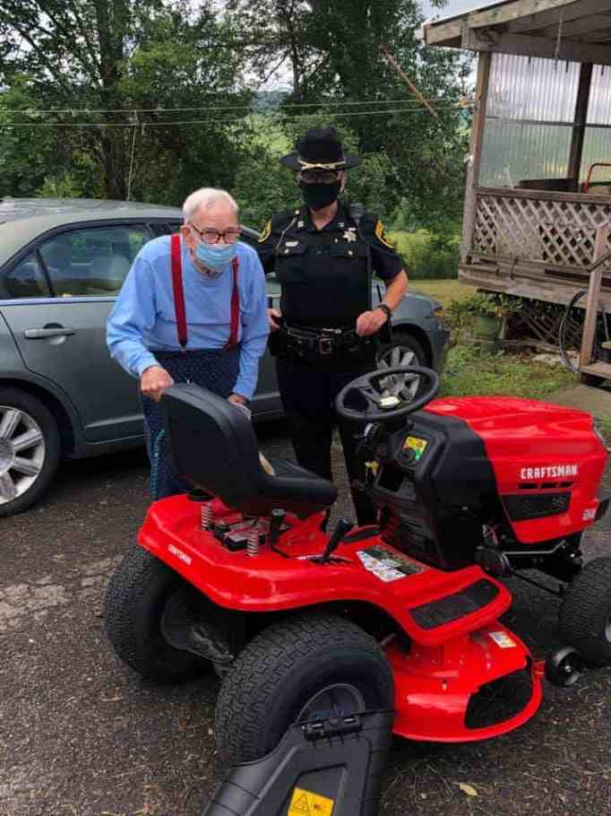 Gordon Blakeslee and a police officer standing behind a brand new mower