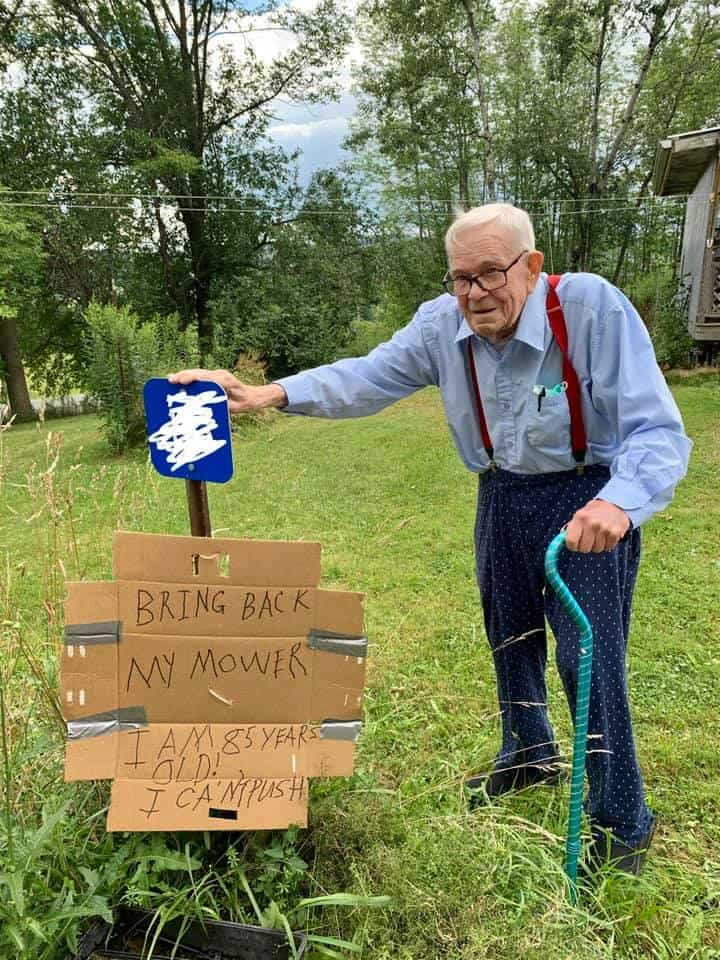Gordon Blakeslee standing on his front lawn with a sign he created