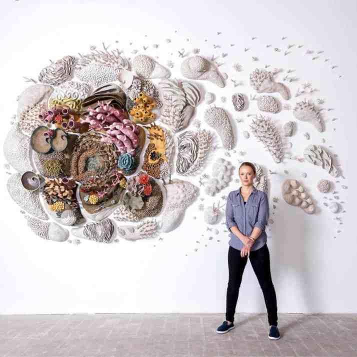 Кортни Мэттисон стоит перед своим керамическим коралловым рисунком.