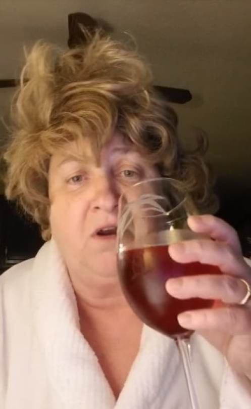 Garnetta Rickett wearing a white bathrobe holding a glass of red wine with her left hand