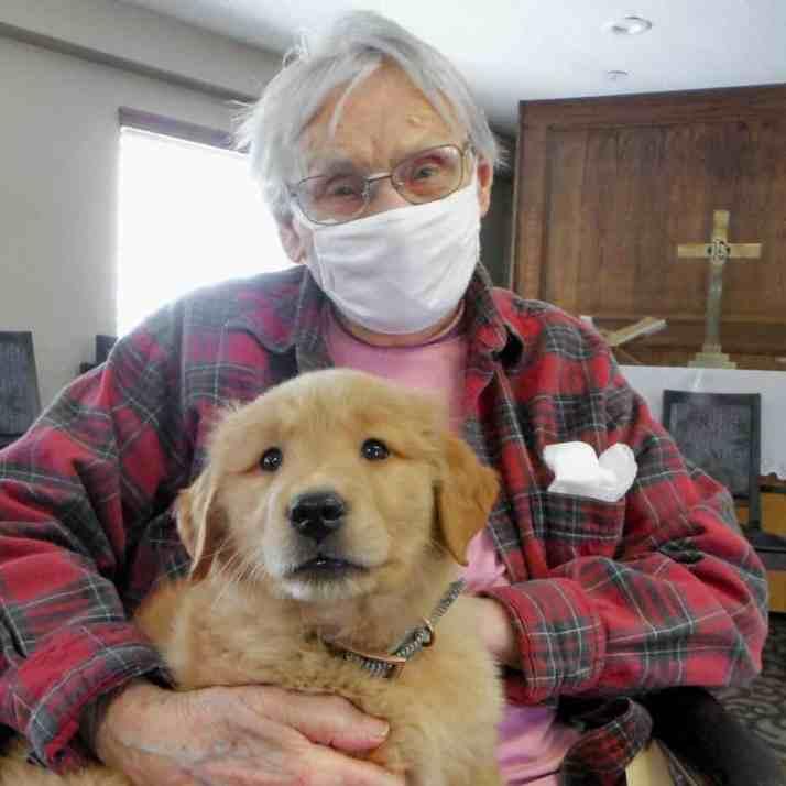Жительница дома престарелых держит золотистого ретривера Грейси
