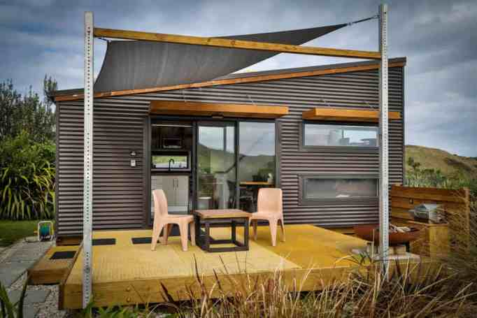 A black tiny house with a deck