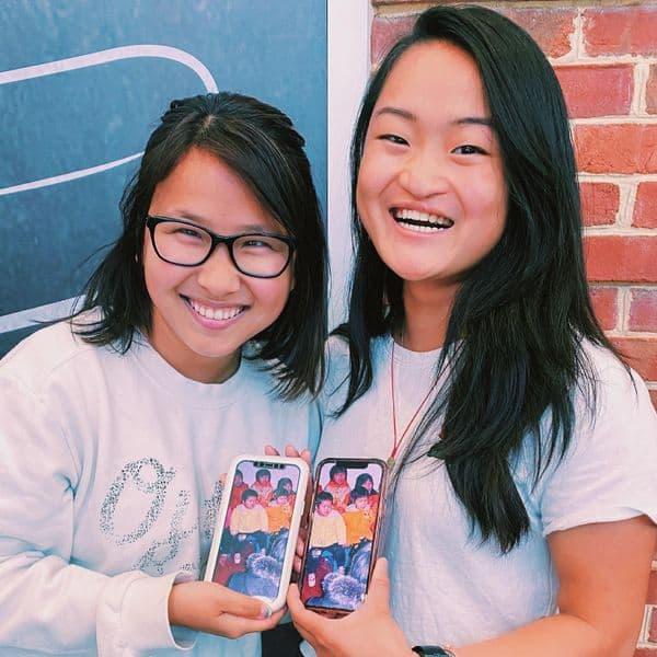 Элли Коул и Руби Вежбицки держат свои телефоны, чтобы показать их детское фото