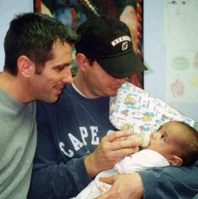 Дэнни Стюарт улыбается малышу Кевину, пока Пит Меркурио держит его