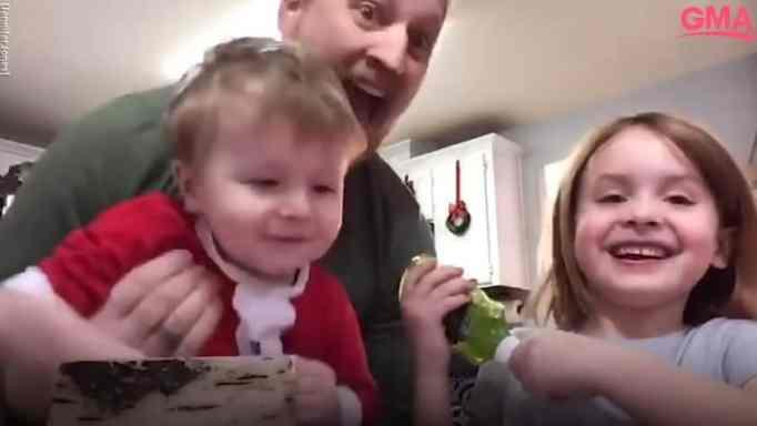 Папа держит мальчика перед камерой, пока его дочь смеется