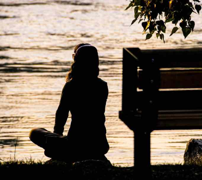 Silhouette of woman contemplating, sittding down.