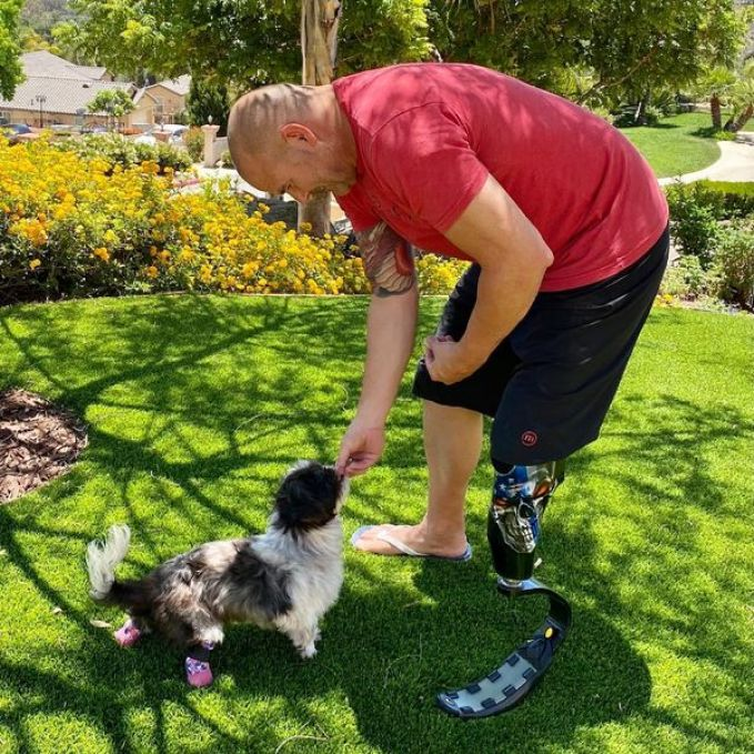 Detective James Hunter giving treats to the shih tzu he adopted