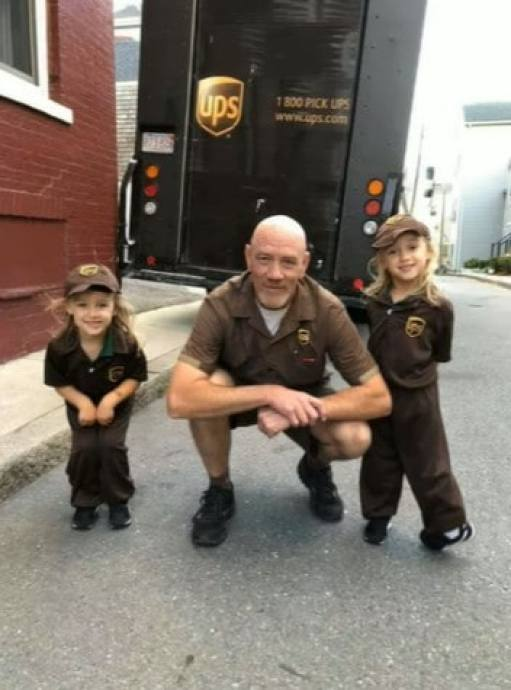 A UPS driver and two kids dressed up like him