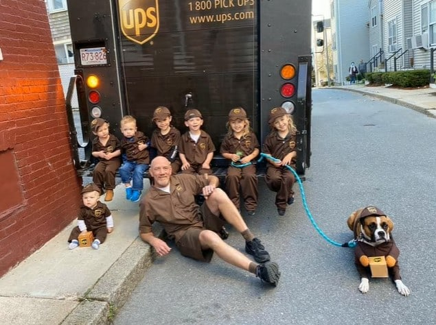 A UPS driver with kids dressed up as him