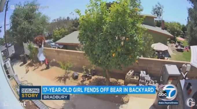 A teen pushing a bear off a wall