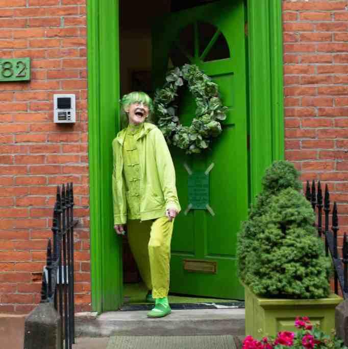 Sweetheart stands before the green door in her home in Brooklyn.