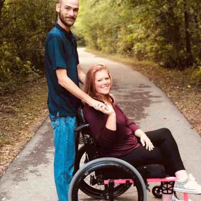 Brittney Hitchcock in a wheelchair with Glen Hitchcock standing behind her