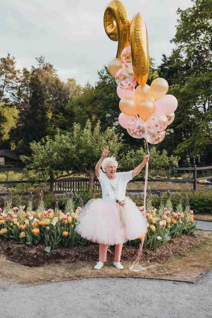 A grandma wearing a pink tutu while holding balloons