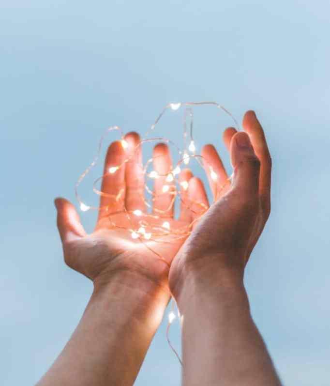 Hands raise holding string lights.