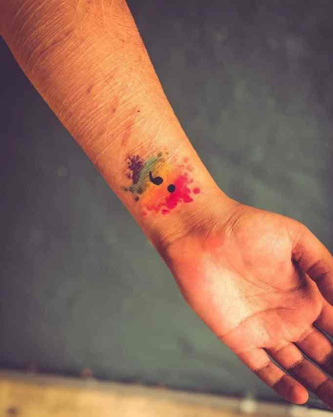 A semicolon tattoo inked on a wrist