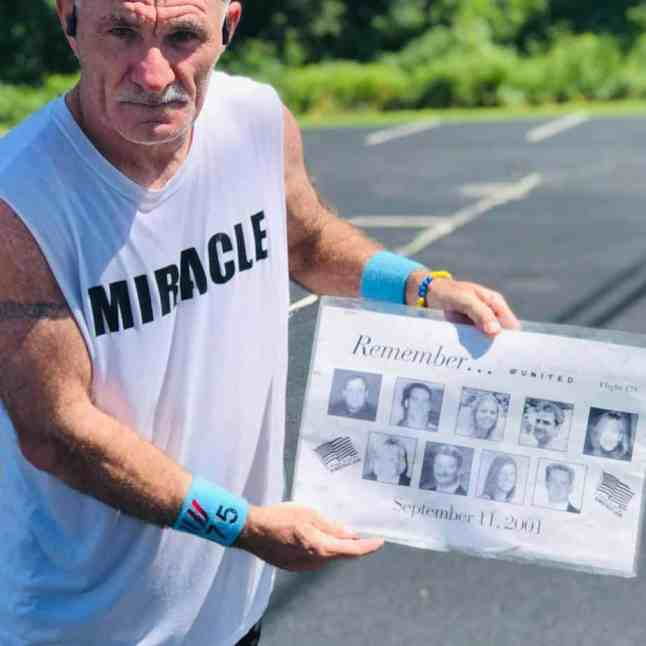 Paul Veneto holding up a card with photos of flight attendants who died during 9/11