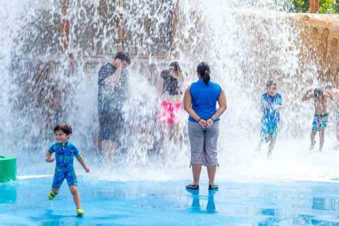 Families enjoy the splash pad at the park