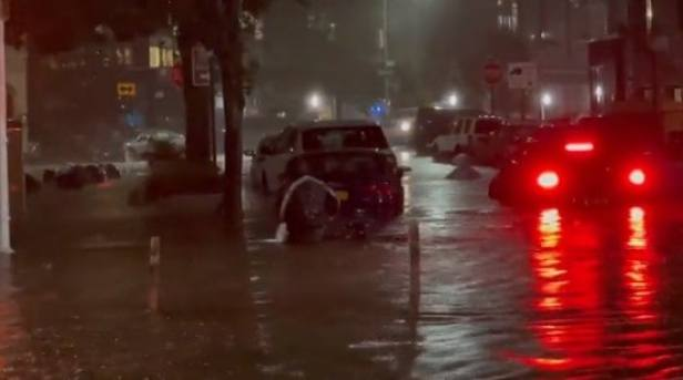 Delivery driver wading through waist-deep water
