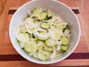 sliced cucumbers and onions in white bowl