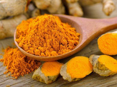 Turmeric and turmeric powder on wooden background